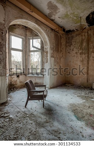 Armchair in the middle of an abandoned warehouse - stock photo