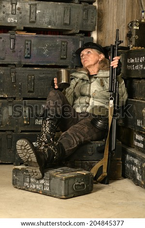 Armed combat female soldier in ammunition with a mug in his hands - stock photo