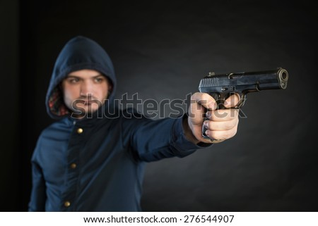 Armed man in a hoodie is pointing a handgun at the target. - stock photo
