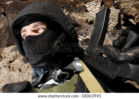 Armed military stands on guard with automatic AK-47 rifle - stock photo