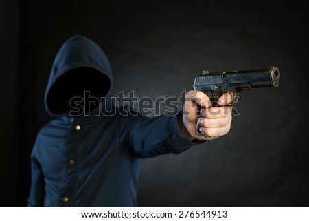 Armed person in a hoodie is pointing a handgun at the target. - stock photo