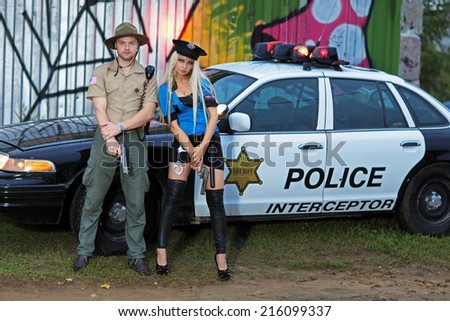 Armed police, a man and woman standing beside his car - stock photo