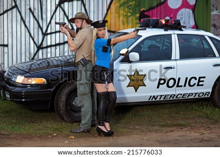 Armed police, a man and woman take measured aim of the gun standing beside his car - stock photo