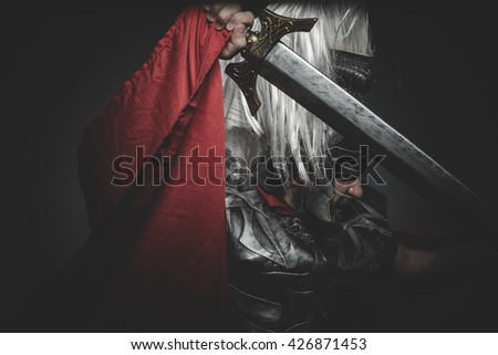 Armed, Praetorian Roman legionary and red cloak, armor and sword in war attitude - stock photo