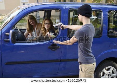 Armed robber robbing women in a car with gun - stock photo