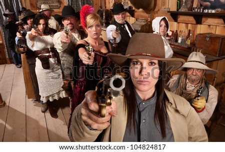 Armed saloon customers with pistols in old western scene - stock photo