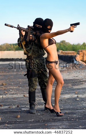 Armed soldier and sexy woman in black masks - stock photo