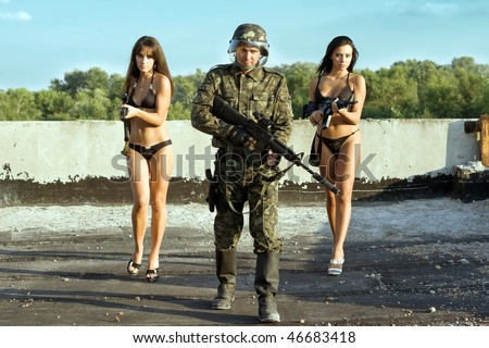 Armed soldier and two women with rifles - stock photo