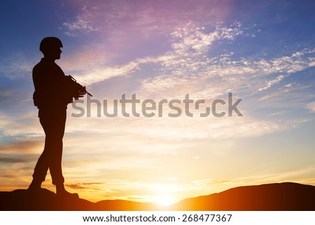 Armed soldier with rifle standing and looking on horizon. Silhouette at sunset. War, army, military, guard. - stock photo