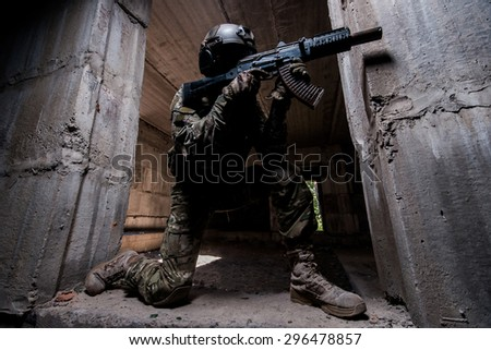 Armed  special forces soldier in mask and helmet aiming a rifle in dark room  - stock photo