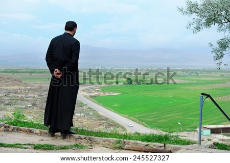Armenian priest overlooking scenic fields and mountains - stock photo