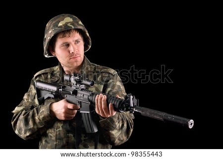 Arming soldier and a rifle in studio. Isolated - stock photo