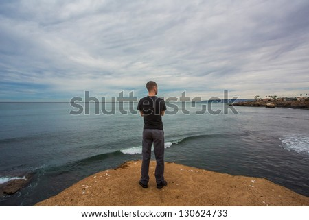 Arms Crossed Looking Away on a Cliff - stock photo