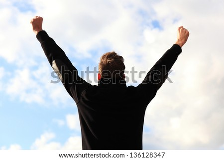 Arms raised in front of a cloudy blue sky. - stock photo
