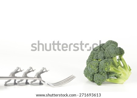 Army Men carry fork to broccoli in childrens healthy eating image - stock photo