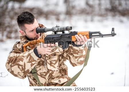 Army military trooper holding gun and shooting enemies on the battlefield - stock photo