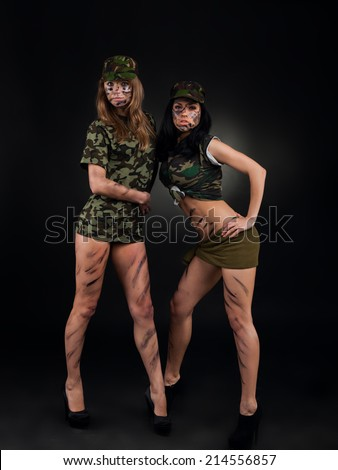 army sexy girls, two long legs soldier woman wear military camouflage uniform cap full length over black background - stock photo