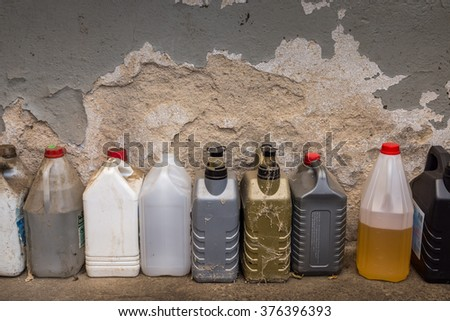 ARNSDORF, GERMANY - FEBRUARY 09 2016: A group of dirty plastic container against a wall, in a workshop. - stock photo