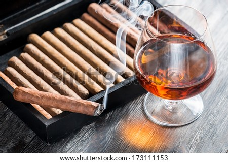 Aroma of cognac and smoking a cigar - stock photo
