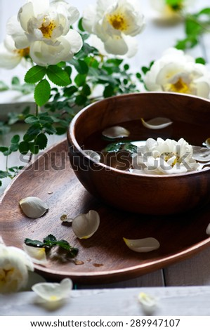 Aroma spa set on white wooden table with white roses, selective focus, vertical - stock photo