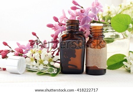 Aromatherapy bottles with essential oils. Fresh blossom. Sweet floral scent. - stock photo