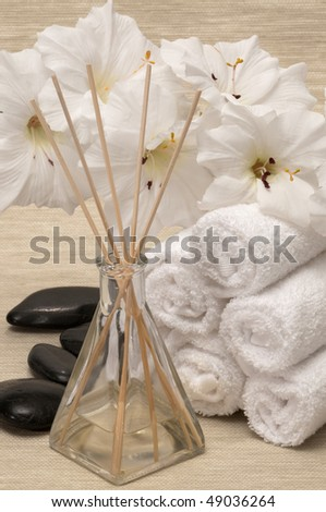 Aromatherapy diffuser towel, rocks and flower in a spa - stock photo
