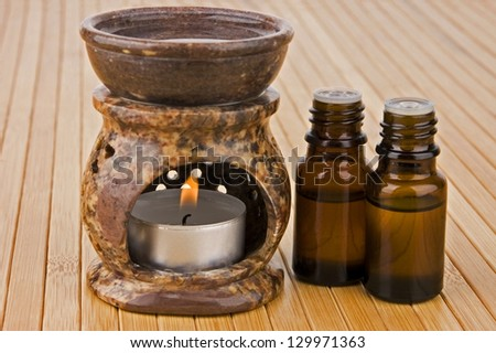 Aromatherapy lamp and oils on bamboo - stock photo