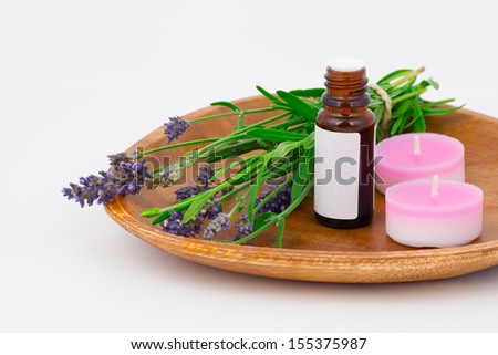 Aromatherapy Lavender oil and lavender flower in the wooden bowl, isolated on white background - stock photo