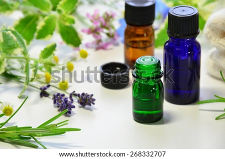 aromatherapy oils with herbal flowers - stock photo