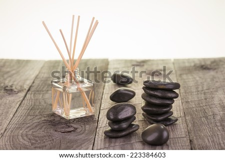 Aromatherapy sticks and black stones on weathered deck close up - stock photo