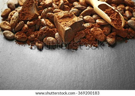 Aromatic cocoa beans and chocolate on grey background, copy space - stock photo