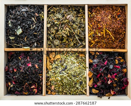 aromatic dry teas in wooden box and spoons on wooden background - stock photo