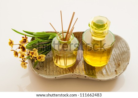 Aromatic essence oil bottle with bottle of fragrance reeds diffuser and bunch orchid flower. - stock photo