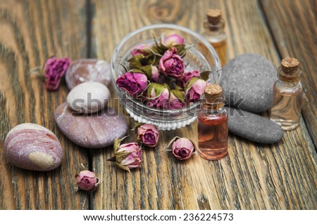 Aromatic essences in small bottles and dry roses in bowl on wooden background - stock photo