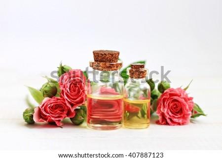 Aromatic essential rose oil in bottles, garden rose flowers. - stock photo