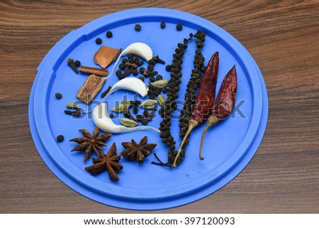 Aromatic Indian spices on blue pate on wooden background in Kerala, India. aromatic Indian spices cinnamon sticks, star anise, garlic, black pepper on the plate. Curry masala preparation - stock photo