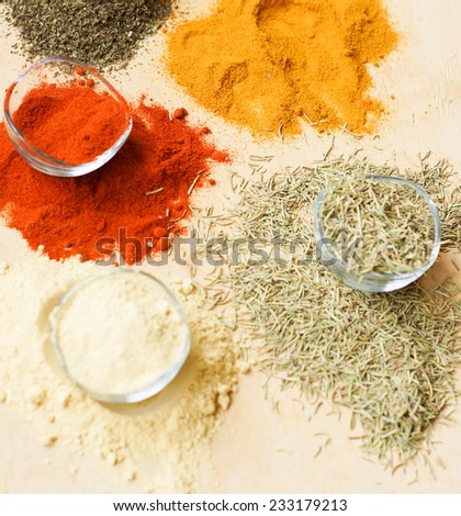 aromatic powder spices on spoons in wooden background - stock photo