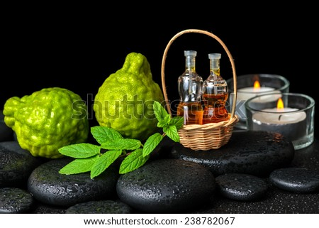 Aromatic spa concept of bergamot fruits, fresh  mint, candles and  bottles essential oil in basket on zen black stones with dew - stock photo
