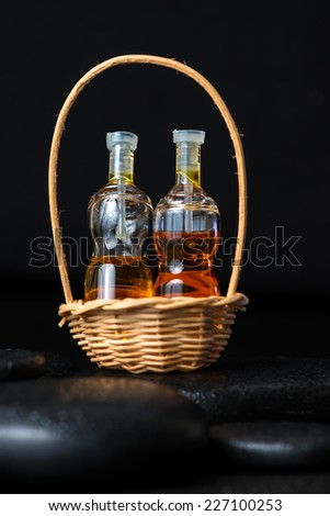 Aromatic spa concept of bottles essential oil in basket on black zen basalt stones with dew, closeup  - stock photo