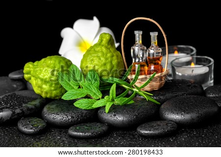 Aromatic spa of bottles essential oil in basket, fresh mint, rosemary, bergamot fruits, flower and candles on black zen stones  - stock photo