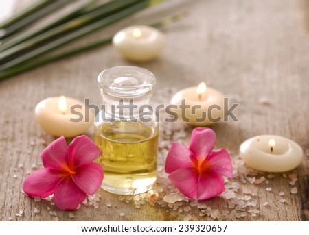 Aromatic spa set with candle , frangipani and oil with pile of salt,   - stock photo