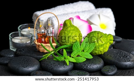 Aromatic spa setting of bergamot fruits, fresh mint, rosemary, candles, towels, flower and bottles essential oil on zen stones  - stock photo