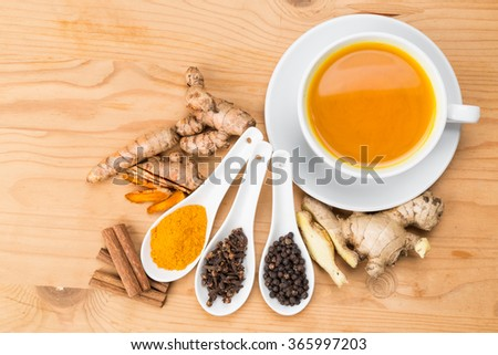 Aromatic turmeric tea with black pepper, cinnamon, cloves and ginger offers many wellness health benefits - stock photo