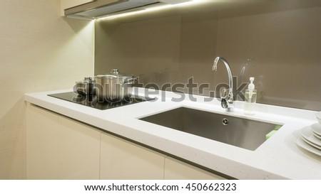 Arranged kitchen pot and kitchen sink on kitchen cabinet - stock photo