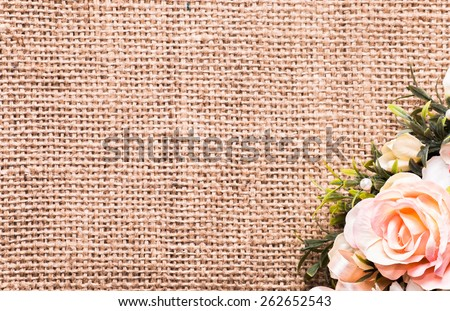 Arrangement of artificial flowers located on burlap background, closeup, useful as background, wedding invitation and greeting card - stock photo