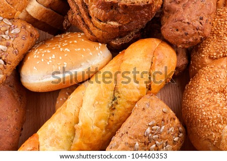 Arrangement of baked bread and rolls closeup on wooden background - stock photo