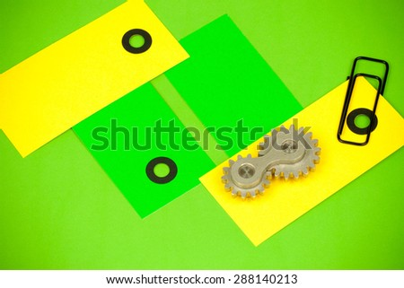 Arrangement of double cog wheel element with vibrant cards and black paperclip, showing funny playful approach to mechanical dynamics theoretical sciences and heavy machine industry terms and items - stock photo
