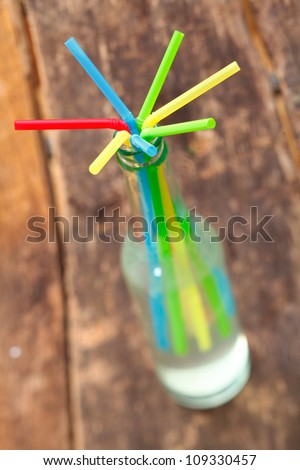 Arrangement of drinking straws radiating from the neck of a glass bottle containing a fruit drink with shallow dof - stock photo