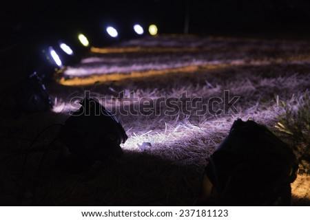 Arrangement of floodlights on lawn for synchronized displays of trees at night (selective focus and shallow depth of field) - stock photo