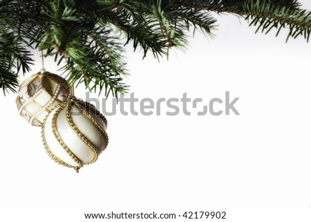 Arrangement of golden Christmas baubles hanging from fir branch, isolated on white background - stock photo